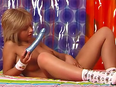 A naked blonde teen is laying on her back on a bed. She is holding a vibrator that she pushes against her nipples. She spreads her legs, moving her pussy in the direction of the camera and massages her clit.video