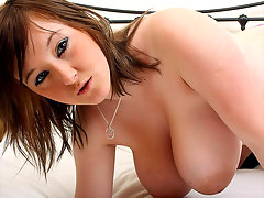 A chubby gilg in a T-shirt and shorts is standing next to a bed. She lifts up her shirt, showing her overflowing bra. A little later she lowers her bra and plays with her giant tits, shaking them about and lifting them in turns.video