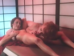 Two naked women are laying on a table. One of them is licking the other ones tits. They move into sixty nine position so they can lick each others hairy pussies. Then one of the girls licks the other one to an orgasm.video