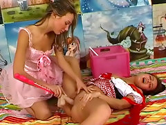 Two teenage girls in carnaval costumes are in the studio. They undress each other partly and then one of them sits down on the floor so the other can fuck her with a dildo. Then the other one lies down and gets fucked with an artificial dick.video