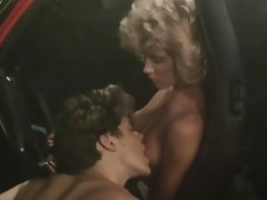 A topless blonde girl is sitting behind the wheel of a car. The door is open and next to her another girl is kneeling down, licking her nipples. Then she takes the first girls trousers off in order to lick her pussy.video
