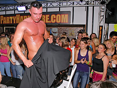 In a ful disco a half naked guy is standing opposite a girl who is sitting on a chair. She gives him a blow job while he covers her head with his coat. A little further on a girl is fucked from behind by a guy.video