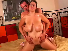 A young girl with big tits is sitting on a bed. She does a slow striptease and when she is completely naked a guy approaches her. She suck his long dick, massaging it with her hands. He then fucks her until he comes over her tits.video