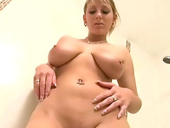 A young girl with large boobs is standing in a bath rub. She is wearing a small bikini and gently squeezes her tits.  She takes her bikini off and pours oil all over her body. Then she turns the shower on and rinses it off.video