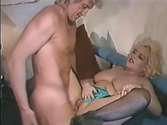 A chubby blonde woman is crouched on her knees on a bed, getting fucked fin her ass by a guy. After a while the guy sits down and she rides his dick, playing with her big tits at the same time.video