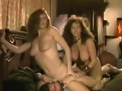 A guy is talking to two busty girls in a bar. Both girls strip down to their panties and one of them dances around. They go to a rom where the girls give the guy a blow job until he fucks both of them in turns.video