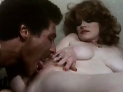 A black guy is receiving a blow job from a redheaded woman. She sits down on a table and spreads her legs so he can lick her pussy. Then he fucks her in various positions, making her moan with pleasure.video