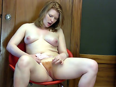 Natural redhead Madison Young strips down to her sexy bare body and plays with her fluffy red haired pussy on the chair.video