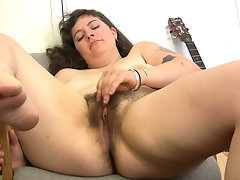 A quick strum and all Esther can think about is her bug fluffy pussy. She drapes her legs over the arm chair and rubs her thick hairy clit.video