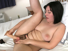Dark haired nympho Raven sucks on her thick rubber dick before arching her back and driving it into her moist meaty bush on the bed.video